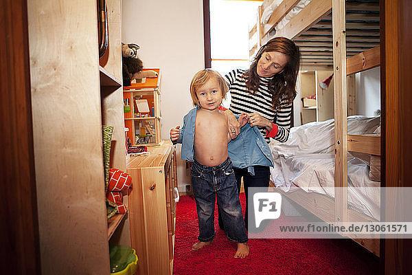 Mutter kleidet Sohn im Schlafzimmer an