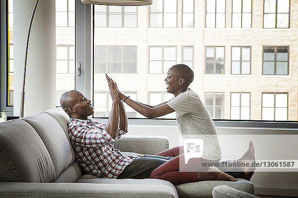 Playful couple enjoying on sofa at home