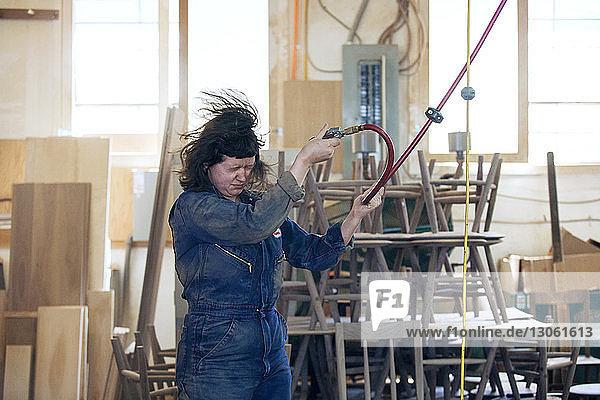 Female carpenter blown by pressure pipe at workshop