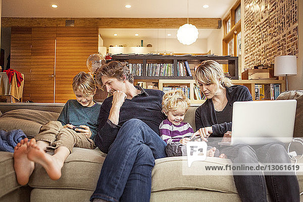 Glückliche Familie sitzt zu Hause auf dem Sofa