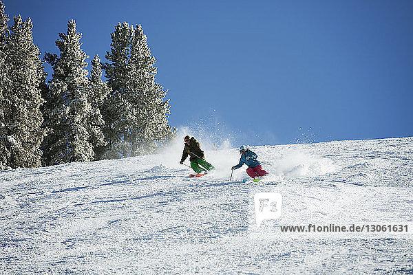Paar Skifahren auf schneebedecktem Berg gegen Himmel