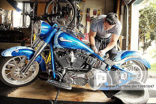 Mann untersucht Motorrad in Werkstatt