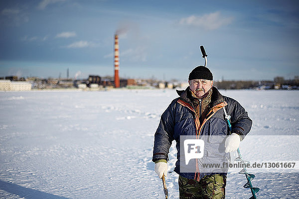 Portrait of senior man carrying drill while walking on frozen lake