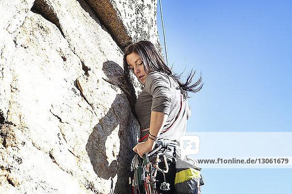 Seitenansicht einer Frau beim Felsklettern gegen klaren Himmel