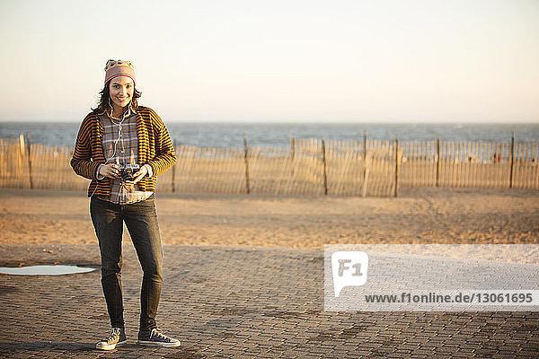 Porträt einer Frau  die eine Digitalkamera hält  während sie auf dem Bürgersteig des Strandes steht