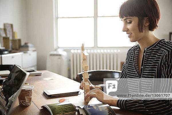 Female photo editor preparing art product at desk in creative office