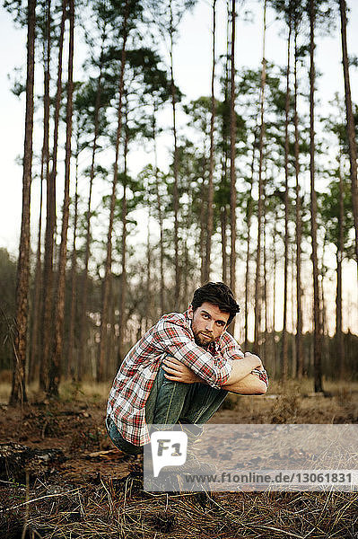 Portrait of man crouching on field in forest