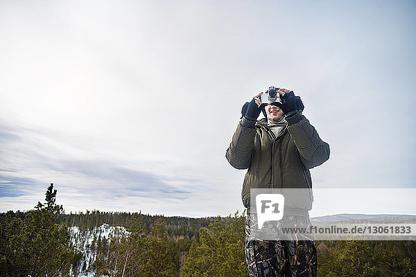 Young man photographing through camera while standing against sky