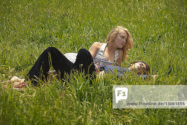 Full length of couple lying on grassy field
