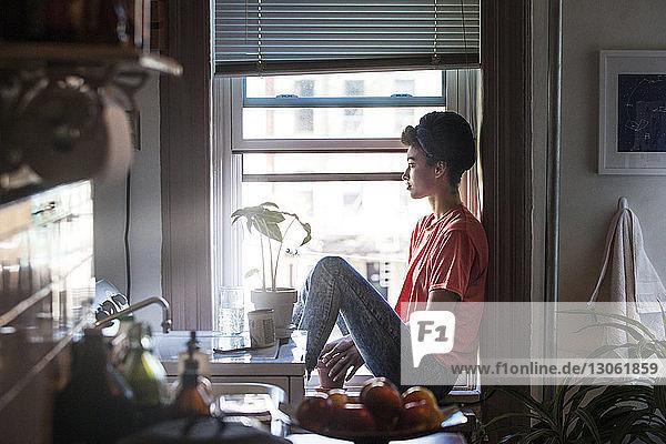 Frau schaut weg  während sie zu Hause auf dem Fensterbrett sitzt