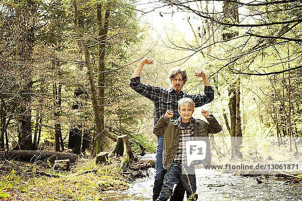 Porträt von Vater und Sohn beim Muskelspiel am Fluss im Wald