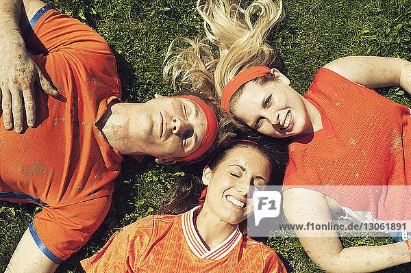 Draufsicht auf Freunde in Sportkleidung  die sich auf einem Rasenplatz ausruhen