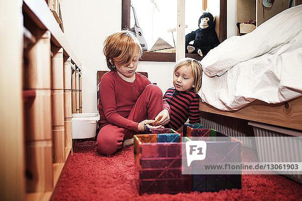 Geschwister arrangieren Spielzeug  während sie zu Hause am Bett sitzen