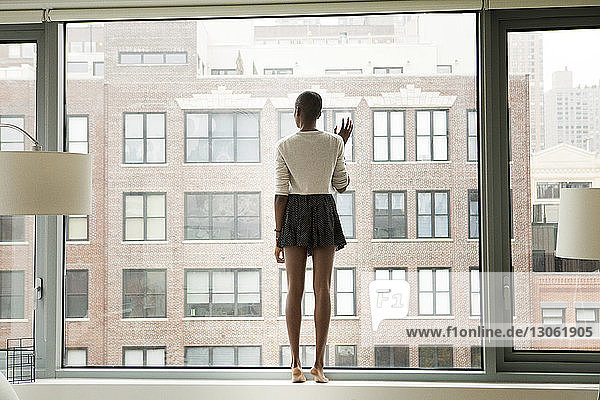Full length of woman standing by glass window at home