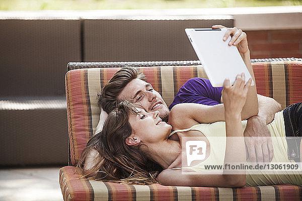 Glückliches Paar benutzt Tablette  während es auf dem Sofa im Garten liegt