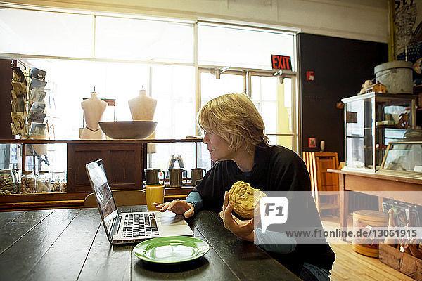 Frau benutzt Laptop  während sie im Café am Tisch sitzt