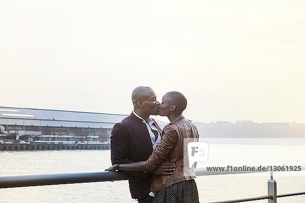 Affectionate couple kissing while standing by railing at pier
