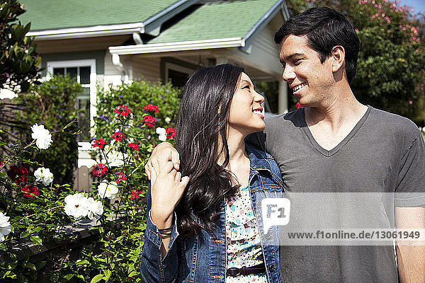Happy couple standing outside house