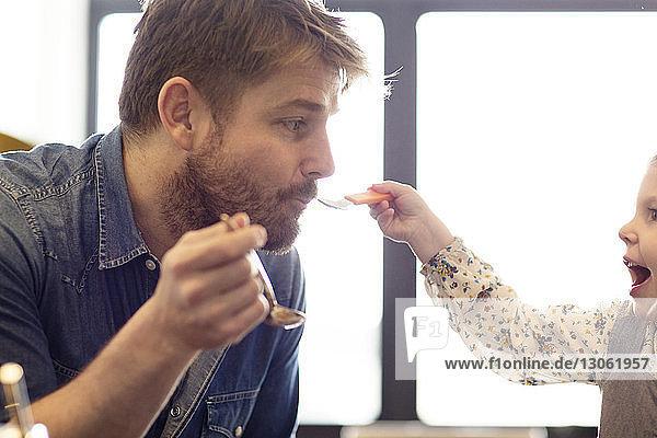 Tochter füttert Vater mit Löffel zu Hause