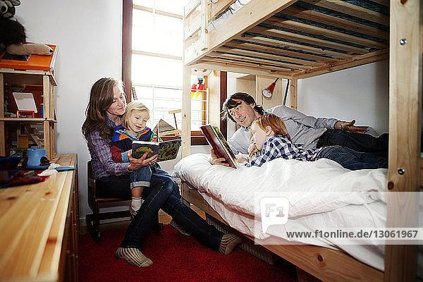 Eltern zeigen Kindern zu Hause im Schlafzimmer ein Bilderbuch