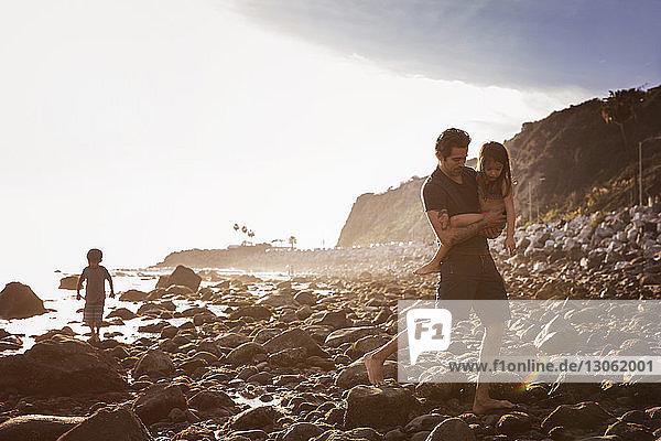 Vater trägt Tochter beim Strandspaziergang auf Felsen