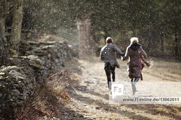 Rear view of couple running on field during winter