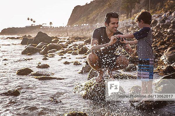 Glücklicher Vater und Sohn genießen am Strand bei Sonnenuntergang