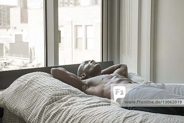 Shirtless man with hands behind head lying on bed at home