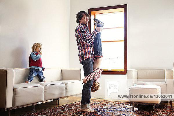 Seitenansicht eines Vaters  der seinen Sohn verkehrt herum trägt  während der Bruder zu Hause sitzt