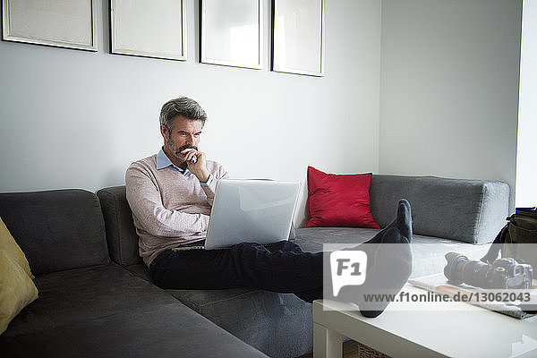 Serious businessman using laptop while sitting on sofa at hotel room