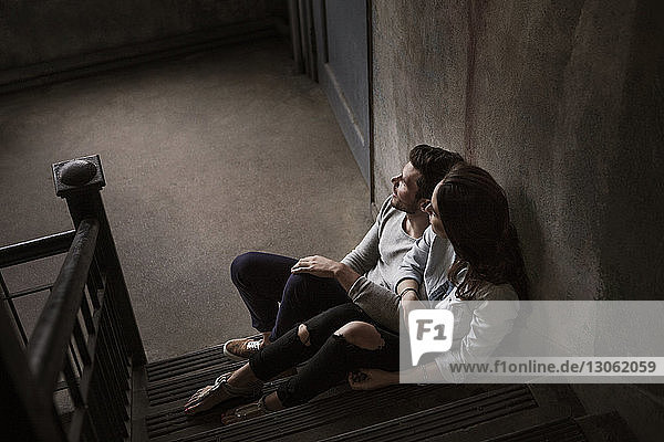 High angle view of couple sitting on stairs at home