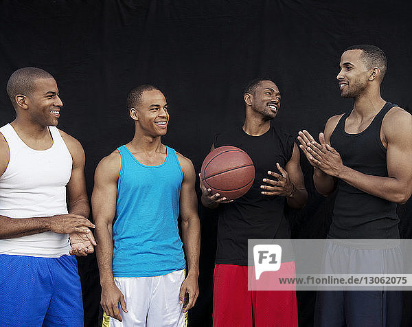 Happy basketball players talking while standing against black wall