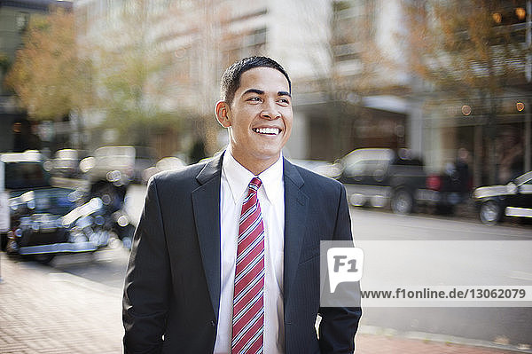 Happy businessman looking away while standing on sidewalk