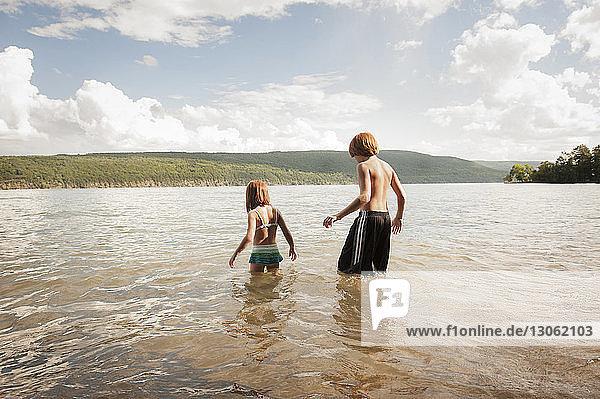 Rear view of siblings in lake against sky