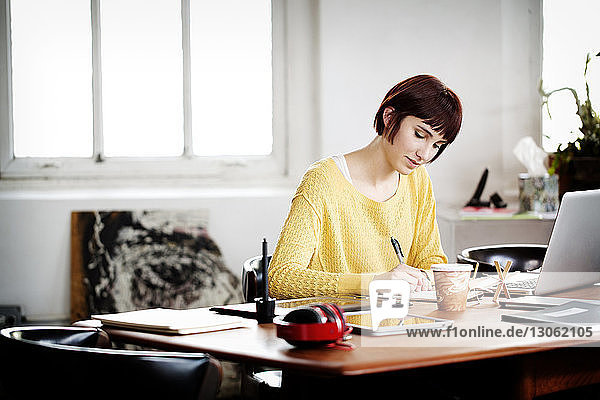 Businesswoman writing in book while working on laptop at desk in creative office