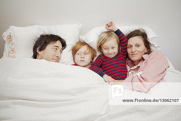 Glückliche Familie liegt zu Hause auf dem Bett