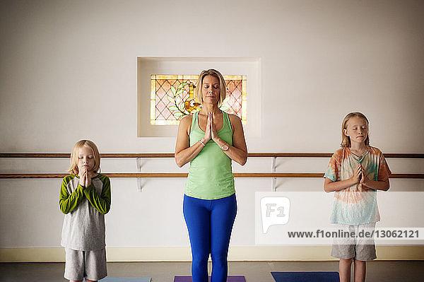 Brüder üben mit Ausbilder im Yoga-Kurs
