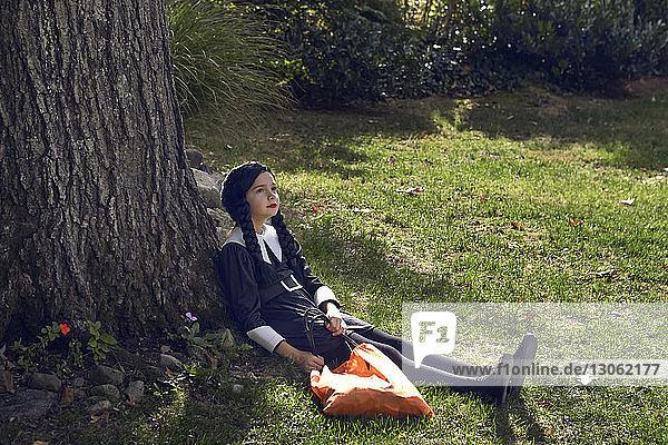 Mädchen in Kostüm sitzt am Baumstamm im Rasen