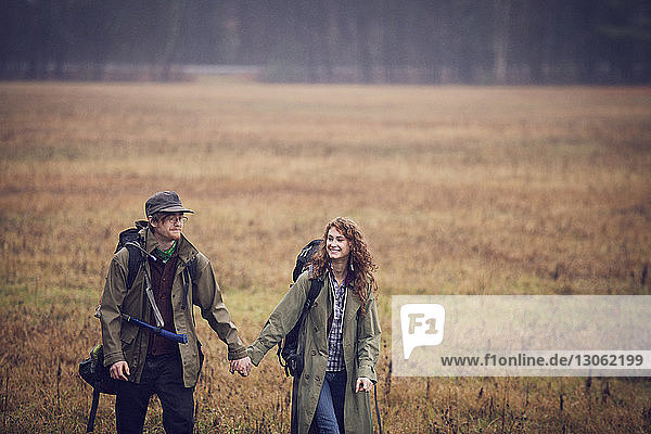 Happy couple holding hands while walking on grassy field