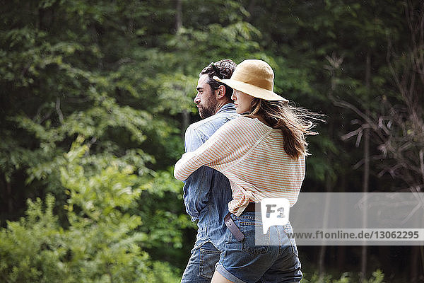Woman embracing man while standing against trees