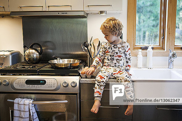 Boy sitting on kitchen worktop at home