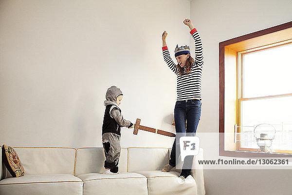 Junge im Ritterkostüm  der das Schwert hält  während er mit seiner Mutter zu Hause spielt