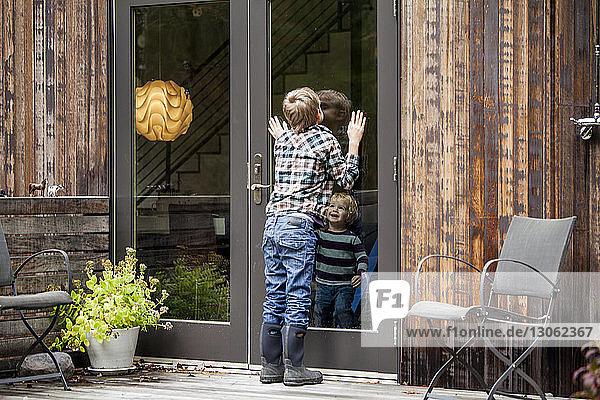 Fröhlicher Junge sieht Bruder durch Glastür an