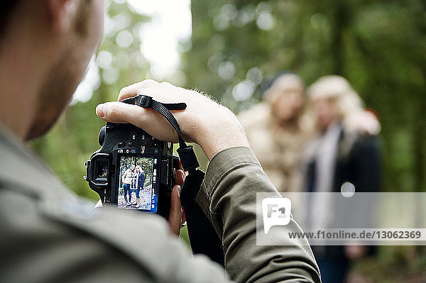 cropped image of man photographing women while standing in forest