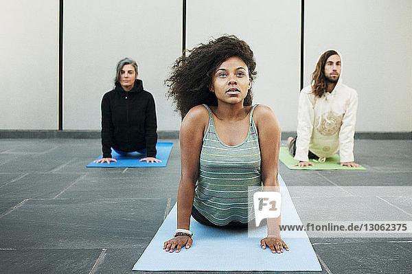 Friends practicing cobra pose in yoga class