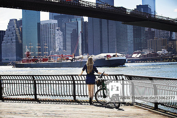 Rear view of woman standing by railing against east river