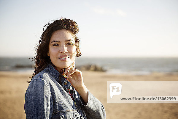 Woman smiling while standing on beach