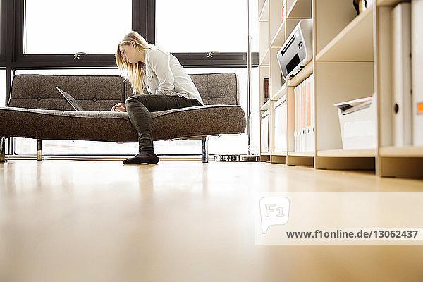 Seitenansicht einer Frau  die einen Laptop benutzt  während sie zu Hause auf dem Sofa sitzt