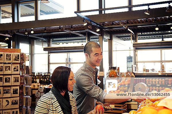 Glückliches junges Paar kauft Obst im Supermarkt