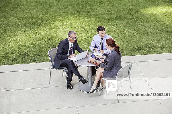 Hoher Blickwinkel auf Geschäftsleute  die am Tisch diskutieren  während sie auf Stühlen sitzen
